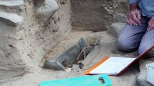 Child's grave covered by stone slabs found at a site (by BBC News)