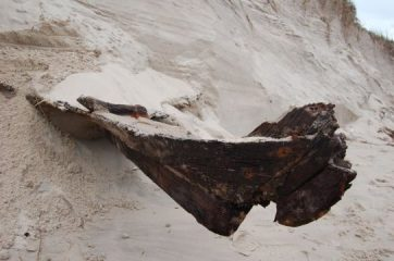 Storm reveals hull of a boat under dune