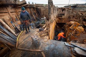 Work to remove mud from the decks of the ship (by CBC News)